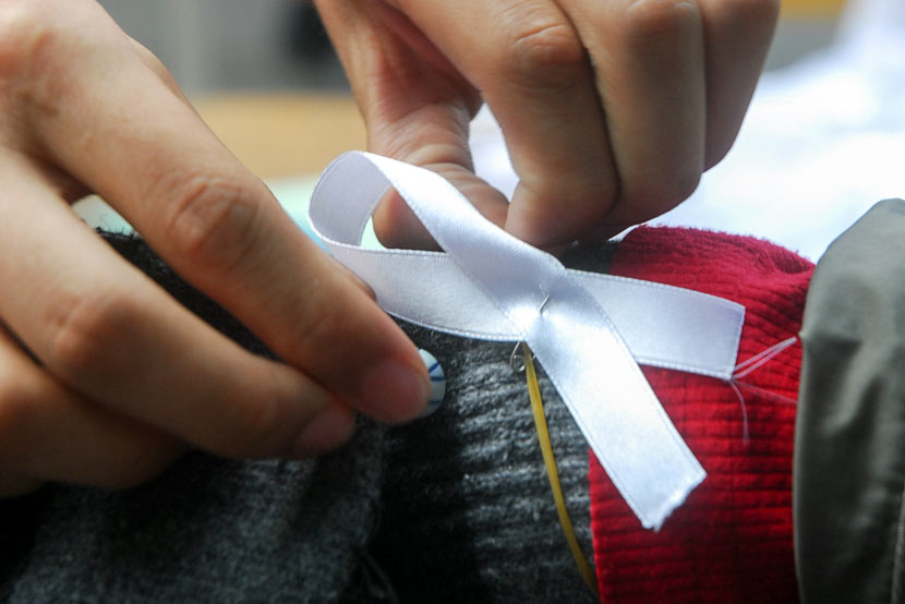 A volunteer attaches a white ribbon, a symbol of anti-domestic violence efforts, to a man's wrist in Haikou, Hainan province, Nov. 25, 2008. Peng Tong/IC