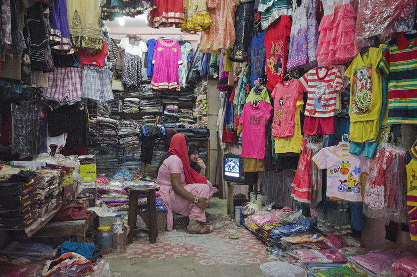 Two women watch TV in their clothing store in Kathmandu, Nepal, May 17, 2015. Sumit Shrestha/IC
