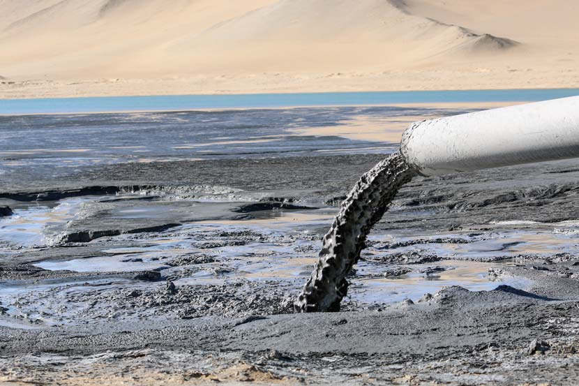 A pipe extending from a factory emits gray liquid waste into the nearby desert in Golmud, Qinghai province, Nov. 3, 2017. Courtesy of Green Data
