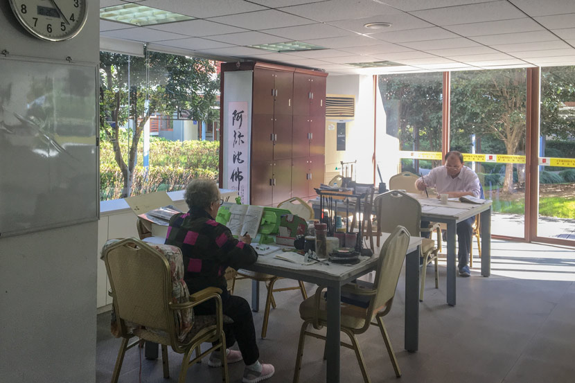 Seniors read and write calligraphy in the activity room at luxury retirement compound Qinheyuan in Shanghai, Oct. 25, 2017. Fan Yiying/Sixth Tone
