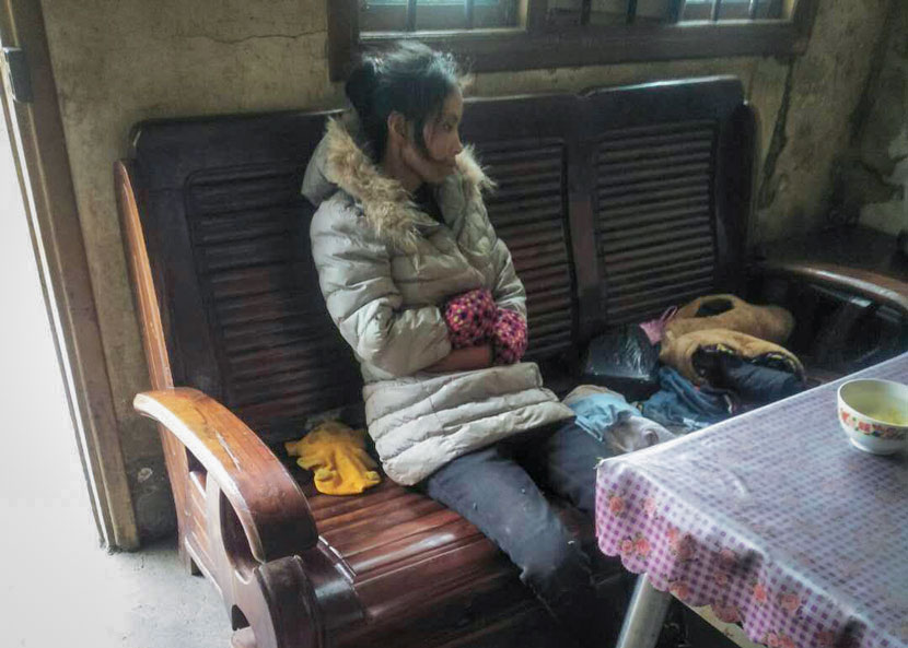 Xiong Wumei sits silently at her parents' home after reappearing in Yanchong Village, Hunan province, Nov. 10, 2017. Courtesy of Xiong Wumei's family