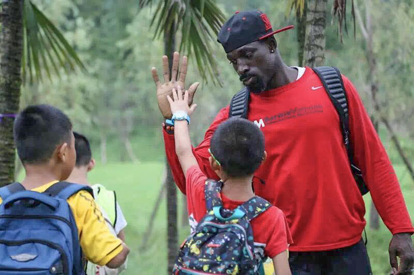 Wendell Brown high-fives a young student during a football camp in Chongqing. Courtesy of Emma Liu