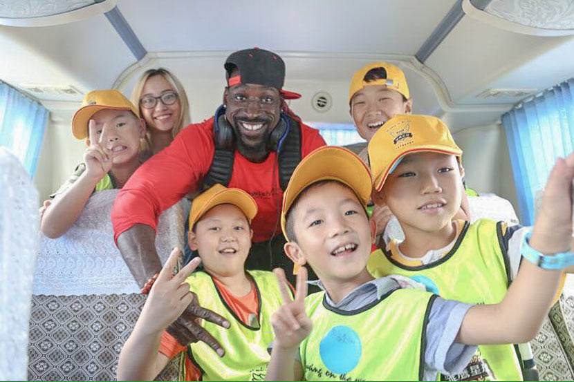 Wendell Brown poses for a photo on a bus with a group of boys participating in a football camp in Chongqing. Courtesy of Emma Liu