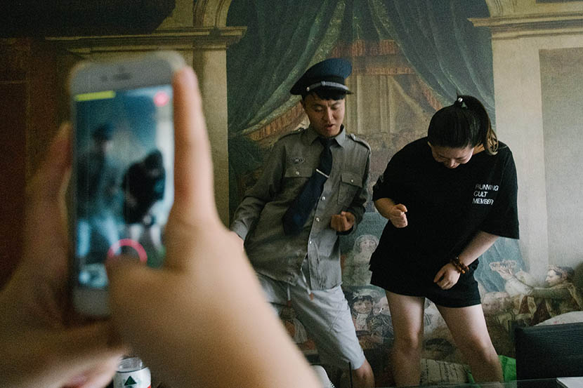 'Errenzhuan' performer You Pengpeng (left) livestreams in a security guard costume with a female duet partner in Nanjing, Jiangsu province, June 19, 2017. Wu Huiyuan/Sixth Tone