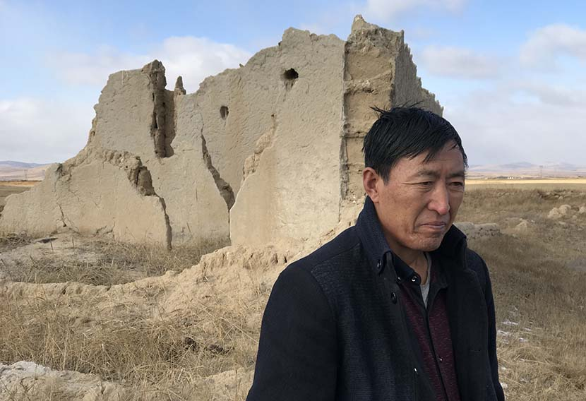 Cheng Guotian stands amid the ruins of his former prairie home, which was demolished in 2002 when his village was relocated as part of ecological migration program, Zhenglan Banner, Inner Mongolia Autonomous Region, Nov. 14, 2017. Colum Murphy/Sixth Tone