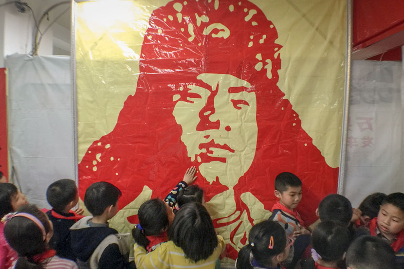 Children look at a poster of Lei Feng at a memorial hall in Hangzhou, Zhejiang province, March 4, 2016. IC