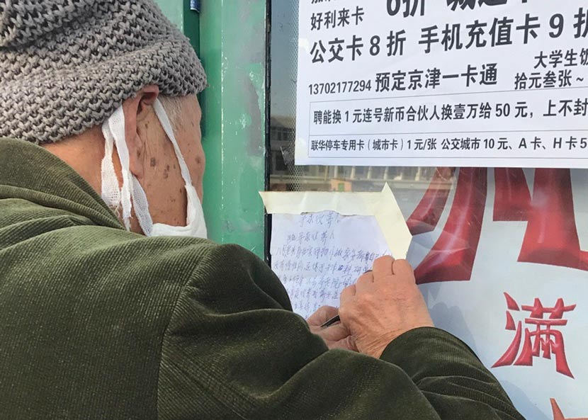 The elderly man, Han, posts adoption fliers at a bus station in Tianjin, Dec. 15, 2017. From Weibo