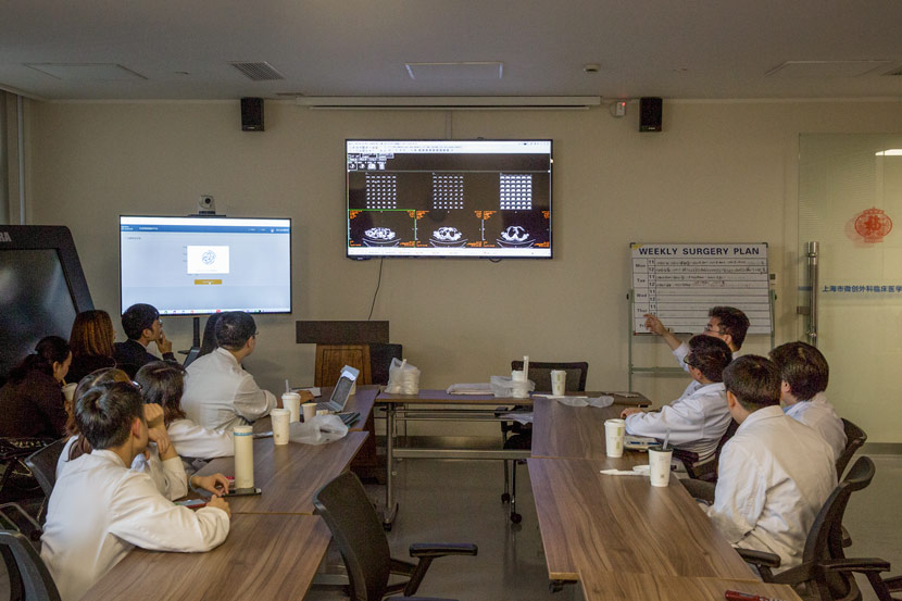 Doctors discuss a bowel cancer case at Ruijin Hospital in Shanghai, Nov. 27, 2017. Staff from IBM's Chinese partner, Hangzhou CognitiveCare, on the left are running the Watson AI system at the same time. Shi Yangkun/Sixth Tone