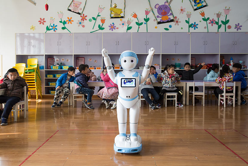 Education robot iPal raises its arms in a classroom at Shunhu Kindergarten in Suzhou, Jiangsu province, Dec. 6, 2017. Shi Yangkun/Sixth Tone