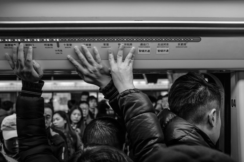 Passengers in a crowded subway car touch the ceiling for balance, Beijing, Dec. 26, 2017. Sun Kai for Sixth Tone