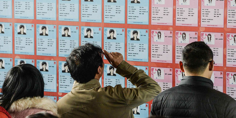 Young singles read fliers bearing the personal information of potential romantic matches, Shanghai, Dec. 20, 2014. Lai Ruining/VCG