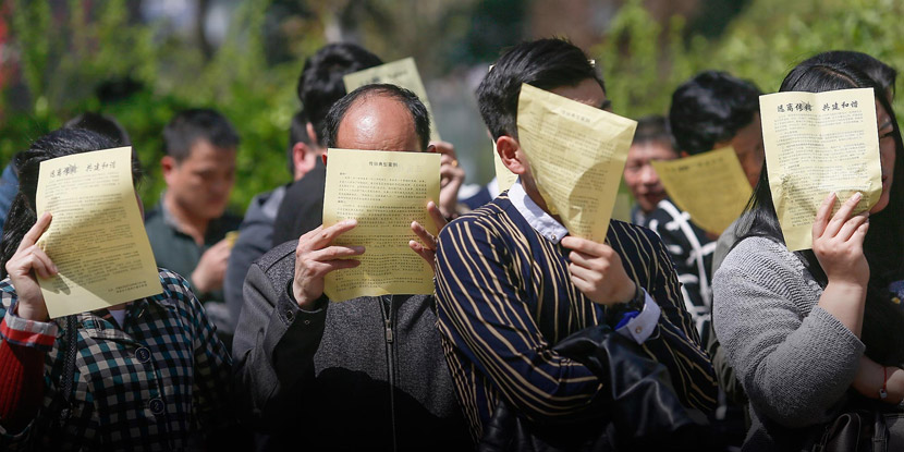 During police questioning, people participating in a pyramid scheme use leaflets to hide their faces from media photographers in Xi'an, Shaanxi province, March 31, 2016. Zhang Jie/VCG