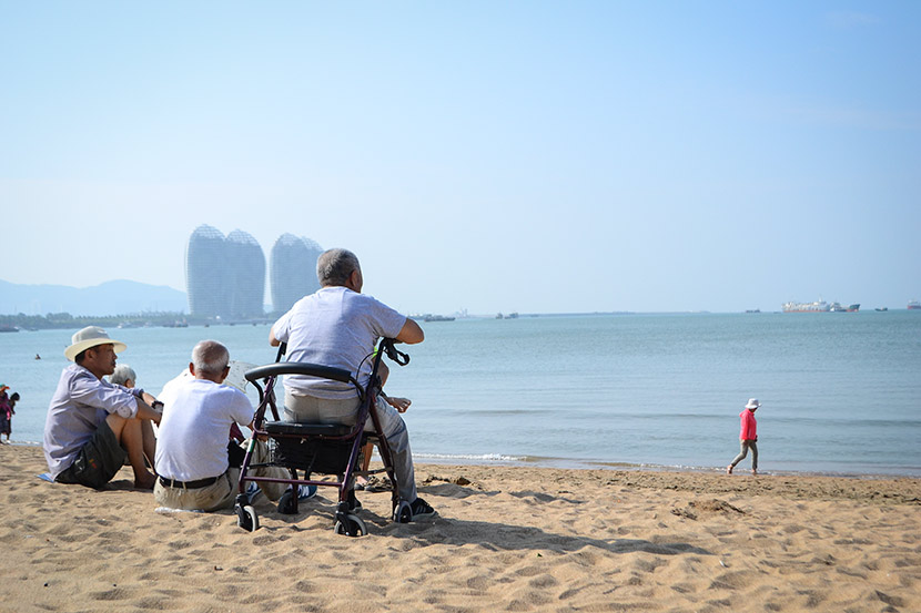 Elderly people enjoy the sunshine on the beach in Sanya, Hainan province, Dec. 8, 2017. Fan Liya/Sixth Tone