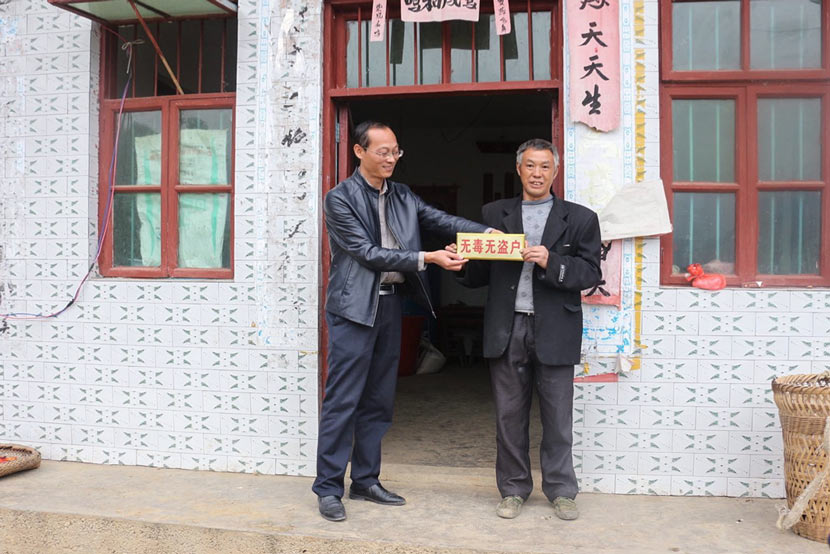 A Banchang Township official (left) awards a local man a 'No Drugs, No Theft' sign for his home in Yanhe County, Guizhou province. Courtesy of the Banchang Township government