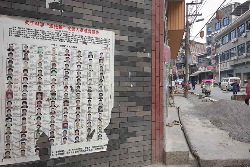 A list of wanted criminal suspects is seen on a wall in Yanhe County, Guizhou province, November 2017. Shao Ke for Sixth Tone