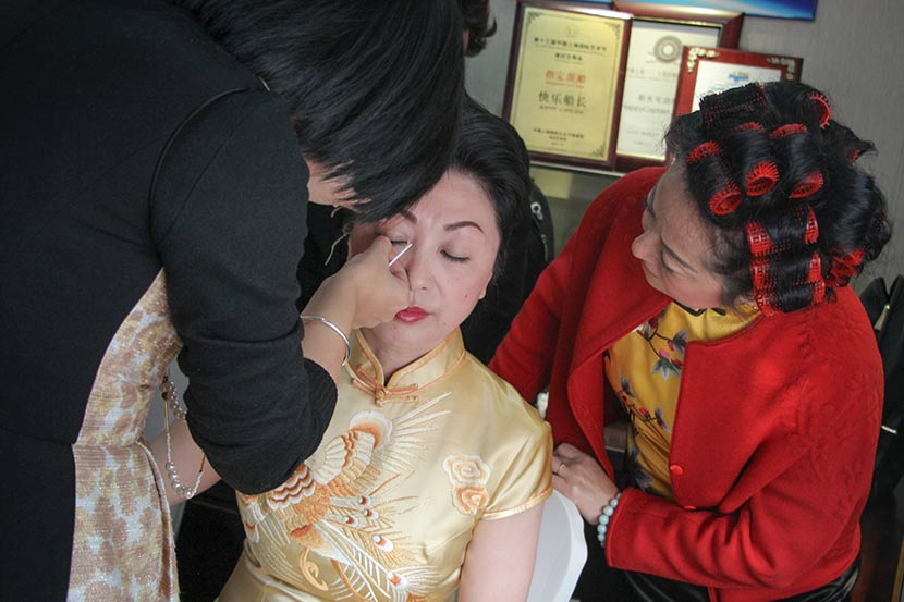 A makeup artist touches up Ni Hong's 1920s Shanghai eyelash look before her performance in Shanghai, Dec. 10, 2017. Joyce Siu/Sixth Tone