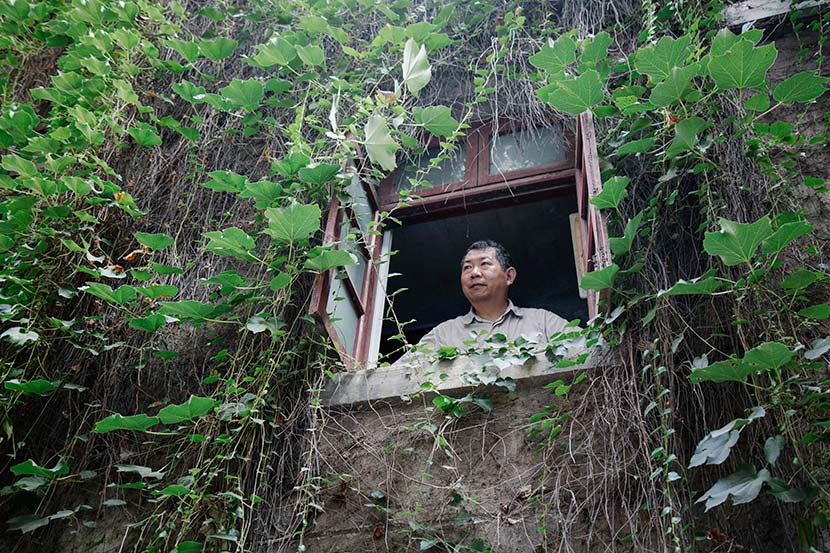 Hu Fusun looks through a window at the house that has belonged to his family for generations, Nanjing, Jiangsu province, July 28, 2017. Wu Huiyuan/Sixth Tone