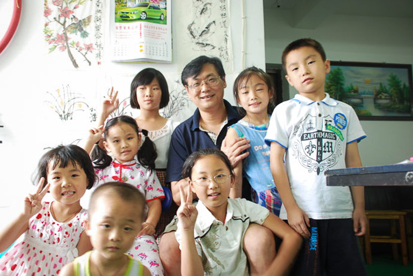 Homeschooling advocate Yuan Honglin and his daughter, Yuan Xiaoyi (center, with glasses), pose for a photo with other 'sishu' students in Haiyan County, Zhejiang province. Courtesy of Yuan Honglin