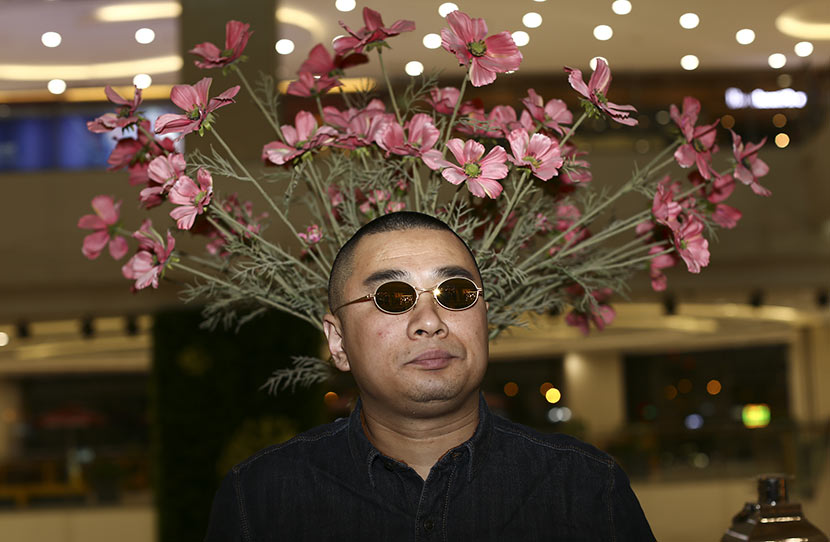 Wang Hai, always wearing a pair of sunglasses, poses for a photo in Beijing, March 11, 2015. Pu Feng/VCG