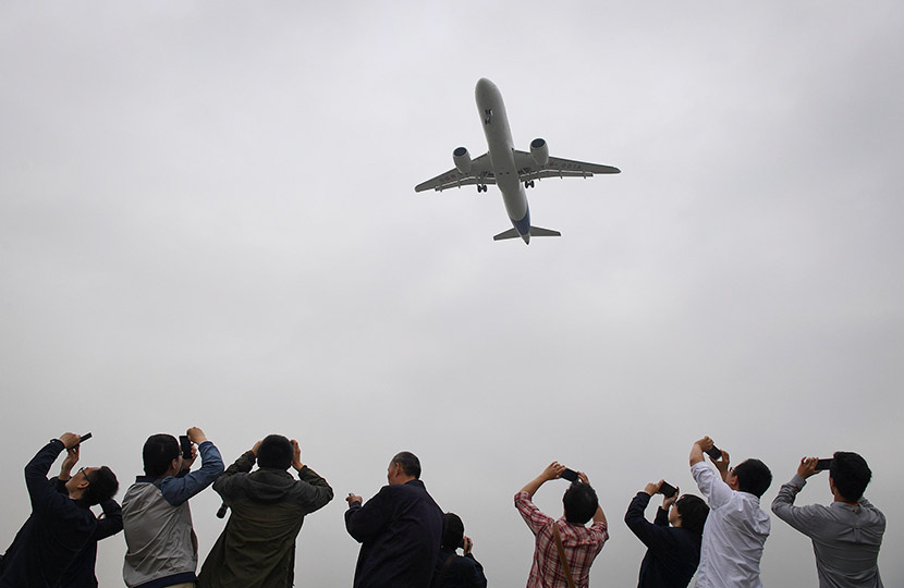 Spectators take photos as they watch the Comac C919, the first Chinese-built large airliner in decades, come in for landing during its maiden flight at Shanghai's Pudong International Airport, May 5, 2017. Greg Baker/Reuters/VCG