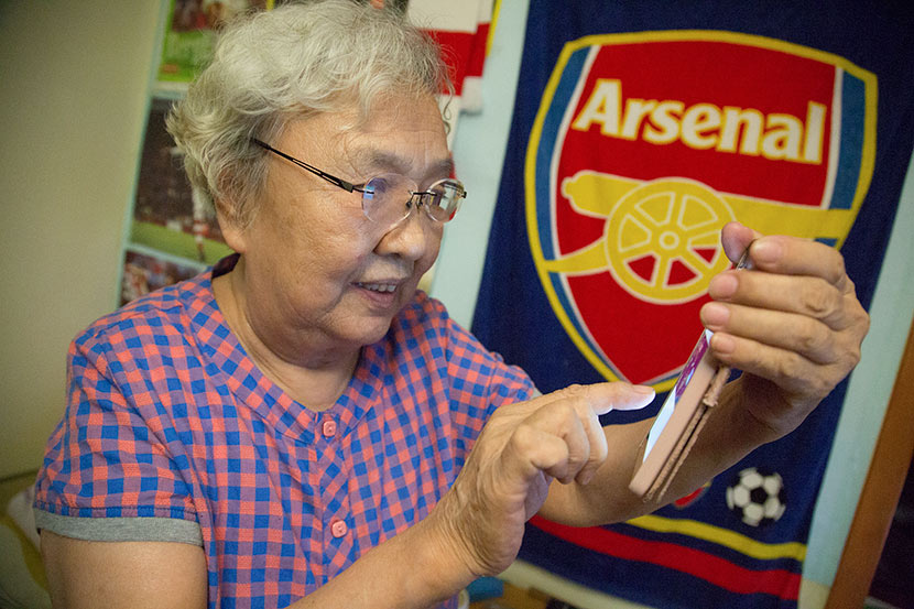 Liu Hongwen, a 79-year-old Arsenal fan known as Grandma Liu, checks Weibo at her home in Beijing after a soccer match, May 28, 2017. VCG