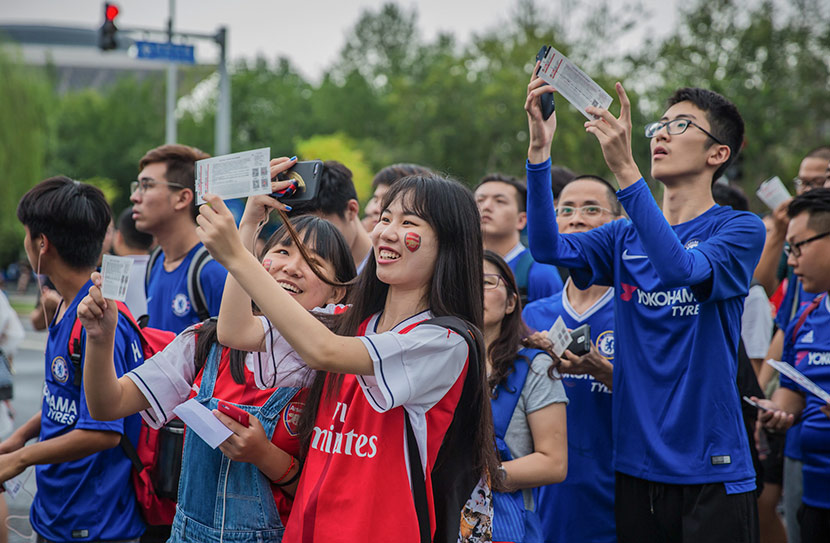 Fans of English soccer teams Arsenal and Chelsea wait to enter the stadium before a match in Beijing, July 22, 2017. Qin Ran/IC