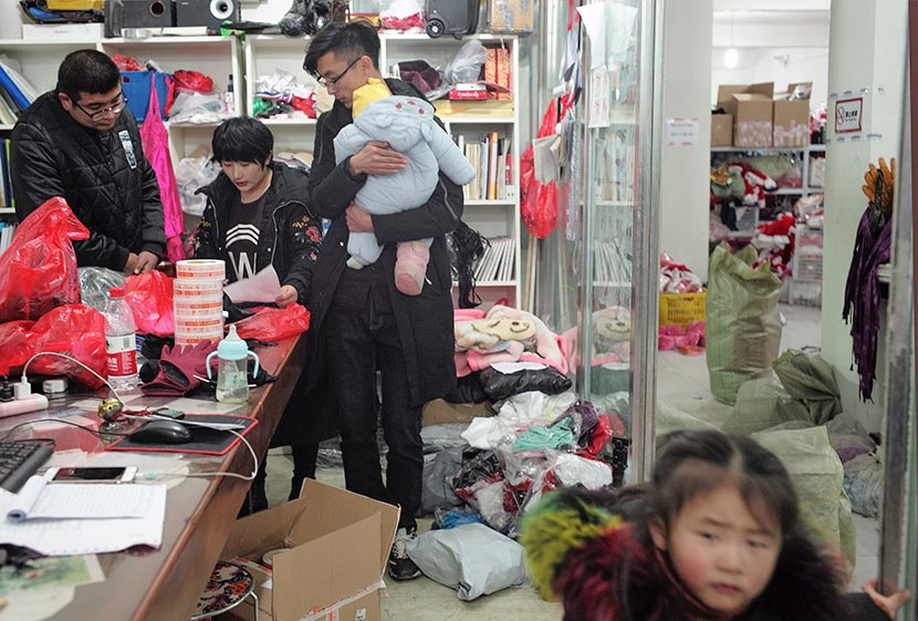 Lei Congrui (center) stands beside his wife at his lingerie warehouse in Guanyun County, Jiangsu province, Dec. 27, 2017. The couple brought their children to work on a busy day at the warehouse. Wu Yue/Sixth Tone