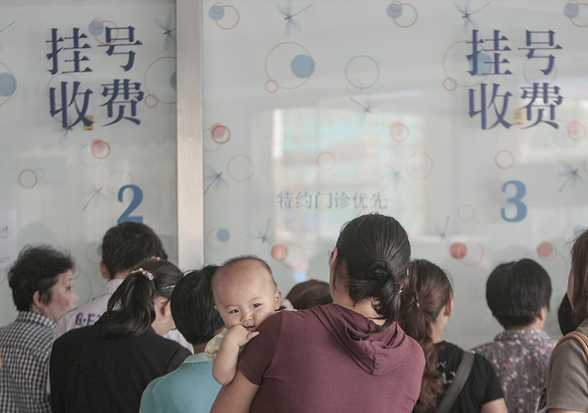 Visitors wait in line to register at a hospital in Nanjing, Jiangsu province, Aug. 4, 2009. An Xin/VCG