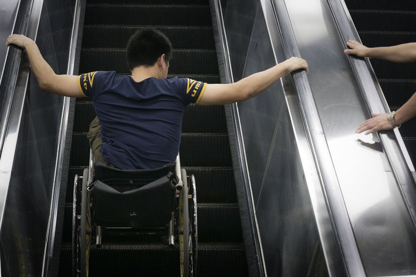 A wheelchair user rides an escalator in Guangzhou, Guangdong province, May 4, 2015. Li Zhanjun/VCG