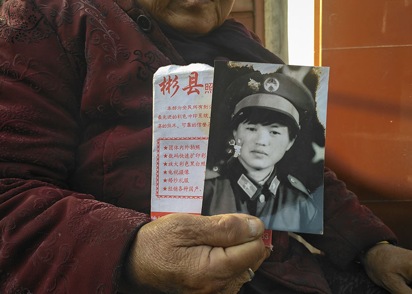 Jing Xixia's mother holds the only portrait of her, which was taken 20 years ago, in Bin County, Shaanxi province, Nov. 7, 2017. Ming Que for Sixth Tone