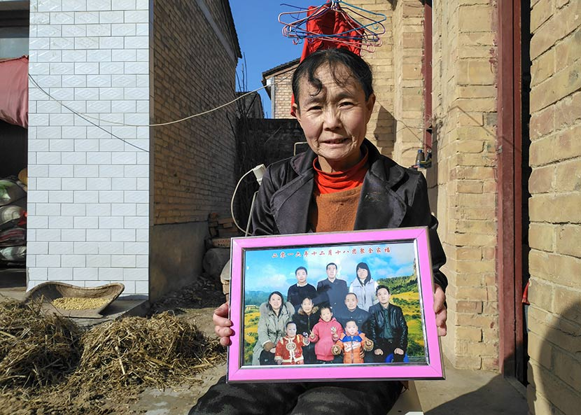 Li Xiaxia holds a family photo taken in December 2016, which includes her son Dong, near her house in Bin County, Shaanxi province, Nov. 7, 2017. Ming Que for Sixth Tone