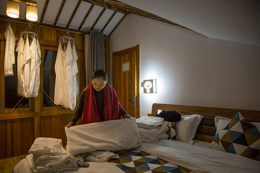 Zhou Qundan folds linens at her homestay in Wencun Village, Fuyang, Zhejiang province, Nov. 16, 2017. Denise Hruby/Sixth Tone