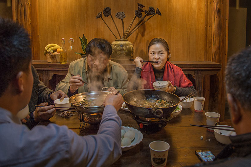 Zhou Qundan (right) eats dinner with fellow villagers in Wencun Village, Fuyang, Zhejiang province, Nov. 16, 2017. Denise Hruby/Sixth Tone
