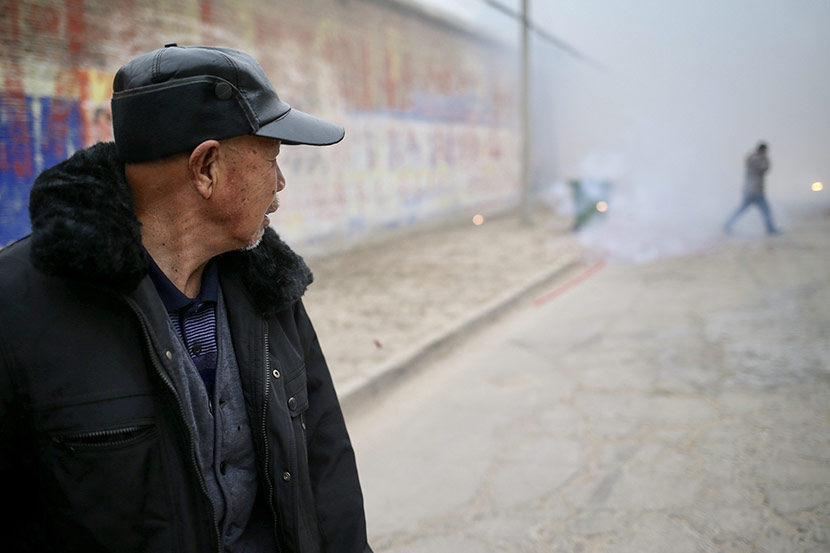 Yang Fengshen watches firecrackers on the main road of Nanyangjiazhuang Village, Dec. 29, 2017. IC