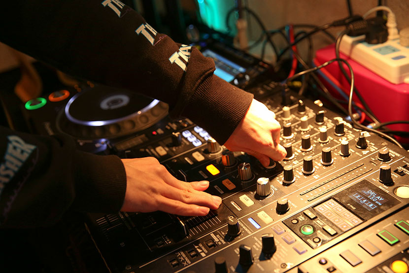 Zhou Yuren adjusts the bass and volume while DJing at beatspot in Shanghai, Jan. 23, 2018. Chan Jacney/Sixth Tone
