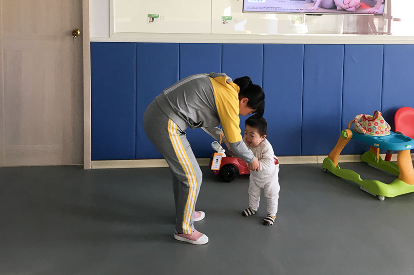 A caregiver helps a child walk at the Nanjing Rainbow Center, Jiangsu province, Jan. 10, 2018. Ni Dandan/Sixth Tone