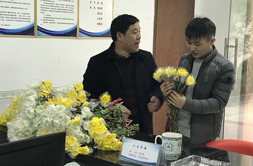 An official gives flowers to a local resident to be used instead of fireworks to commemorate ancestors in Huangcai Town, Hunan province, Feb, 2018. Tan Jun for Sixth Tone