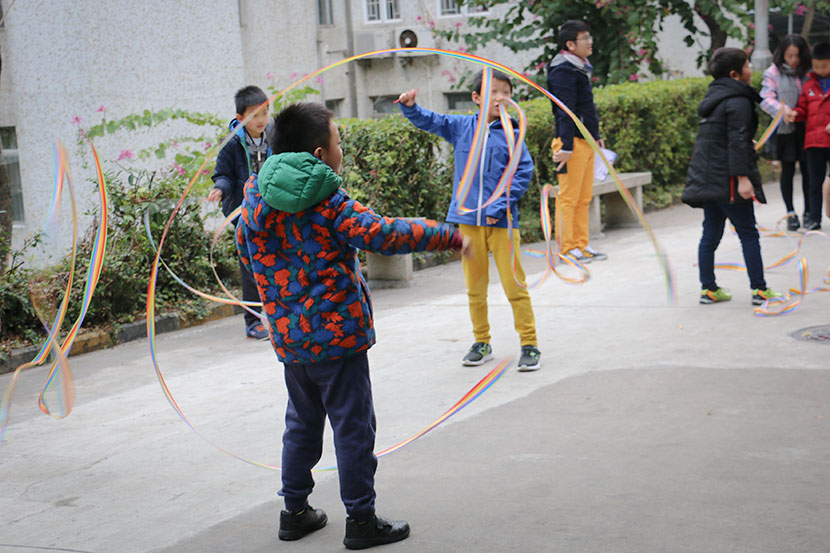 Dyslexic children play with ribbons to improve dexterity in a courtyard next to Weining Dyslexia Education Center in Shenzhen, Guangdong province, Jan. 30, 2018. Cai Yiwen/Sixth Tone