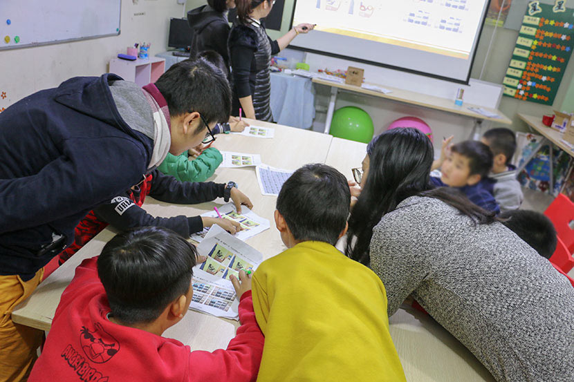 Teachers and volunteers help dyslexic students with schoolwork at Weining Dyslexia Education Center in Shenzhen, Guangdong province, Jan. 30, 2018. Cai Yiwen/Sixth Tone