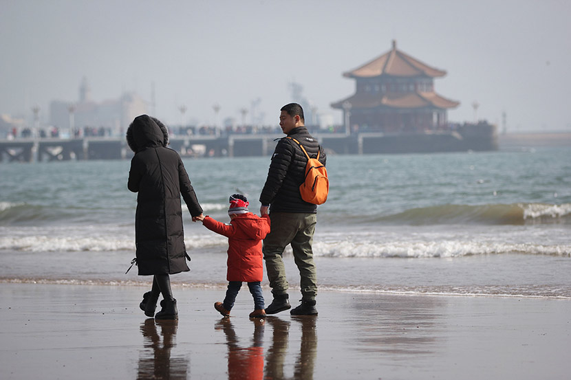 A family of three people visit a tourist spot in Qingdao, Shandong province, Feb. 23, 2018. Huang Xianjie/VCG