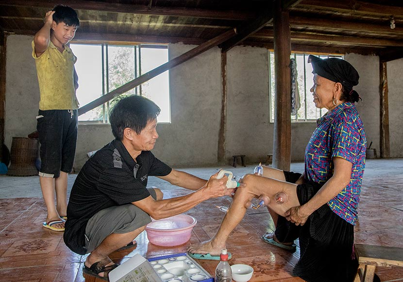Doctor Zhou Zhaosong treats a patient who lives near Pannei Village, Longsheng County, Guangxi Zhuang Autonomous Region. July 27, 2017. Stefanie Schweiger for Sixth Tone