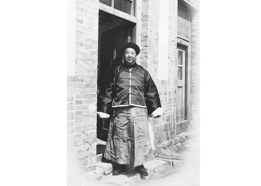 A Qing-dynasty local official dressed in his uniform poses for a photo outside a single-story house with glass-paneled windows and doors, in Yantai, Shandong province, in the early 1900s. Courtesy of 'Old Photos'
