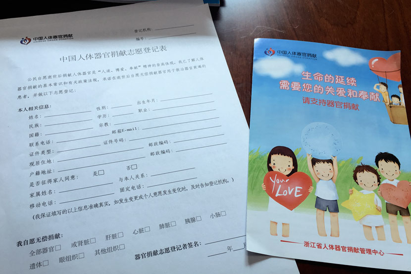 An organ donation form sits on a table alongside a pamphlet promoting organ donation in Quzhou, Zhejiang province, Feb. 1, 2018. Ni Dandan/Sixth Tone