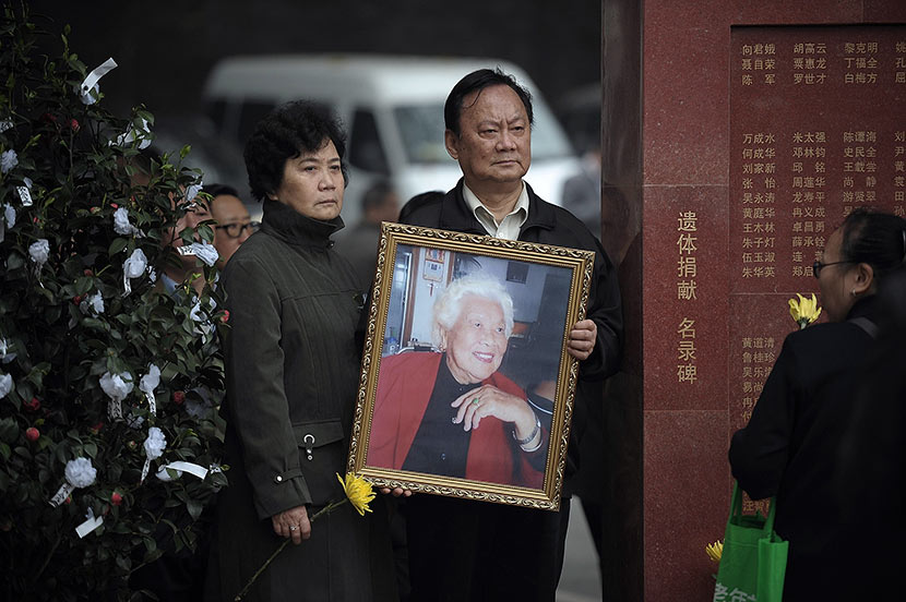 A relative holds a portrait of an organ donor in front of a monument bearing donors' names at a memorial park in Chongqing, April 4, 2014. Ran Wen/VCG