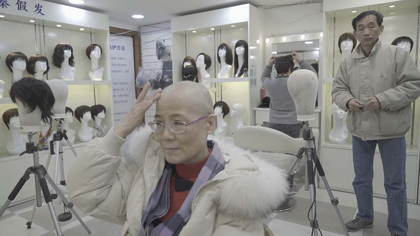 Xu Wenyu, a cancer patient, touches her head before trying a wig at Pinqin wig shop in Shanghai, Jan. 29, 2018. Wu Yue/Sixth Tone