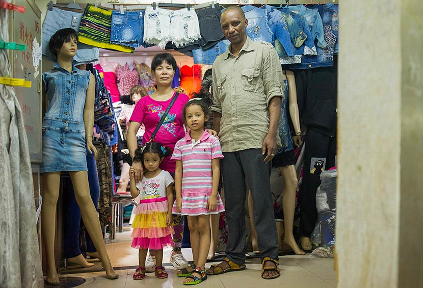 Bah Abdullaye (right), 42, and his Chinese wife pose for a photo with their daughters at their clothing stall in Guangzhou, Guangdong province, July 15, 2014. Dave Tacon/Polaris/VCG