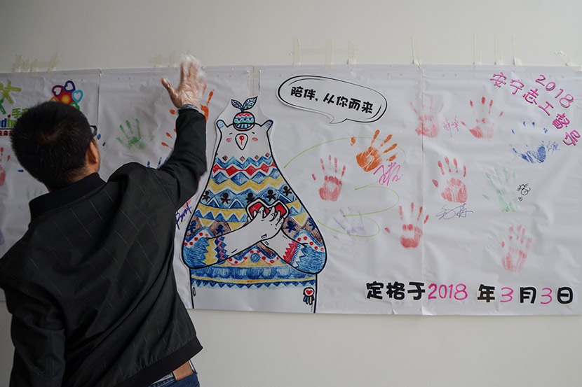 A volunteer puts his handprint on a banner at Hand in Hand's training event in Shanghai, March 3, 2018. Fan Yiying/Sixth Tone