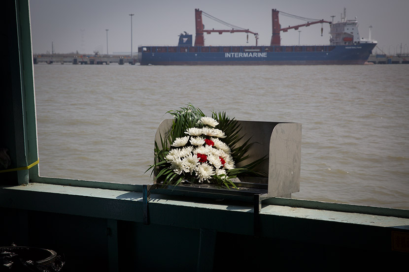 A bouquet sits on a metal chute used for scattering the deceased's ashes during a sea burial in Shanghai, April 1, 2018. Shi Yangkun/Sixth Tone