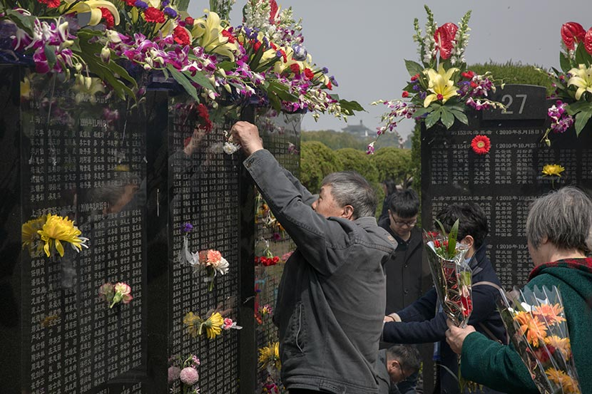 A man places flowers on a monument for people buried at sea in Binghai Ancient Garden Cemetery, Shanghai, March 24, 2018. Shi Yangkun/Sixth Tone