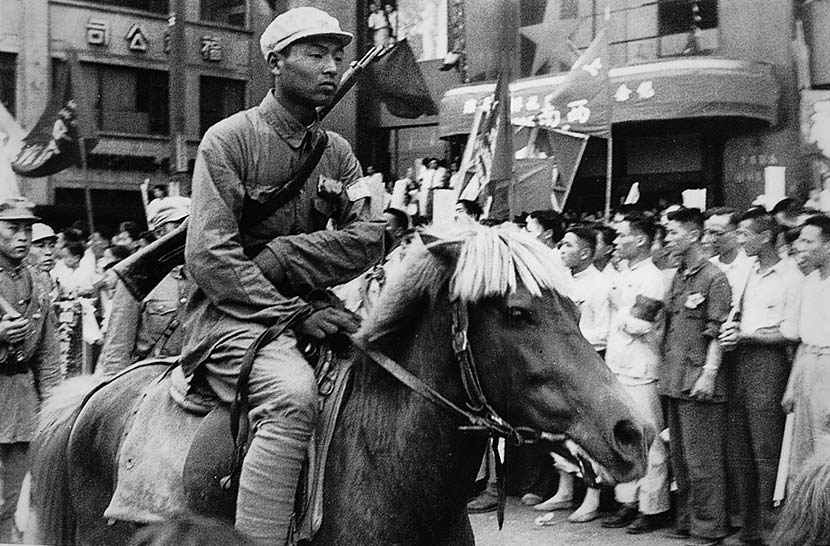A young soldier rides through downtown Shanghai rides on horseback, while a rifle slings over his back in Shanghai, May 1949. Courtesy of 'Old Photos'